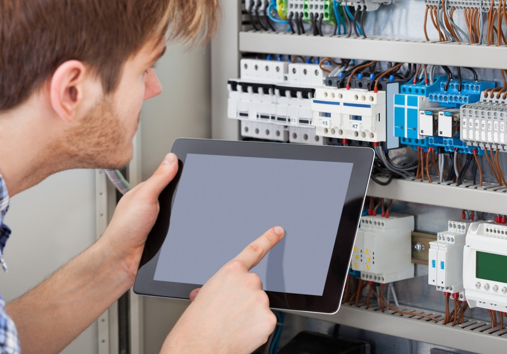 Technician Examining Fusebox Using Tablet